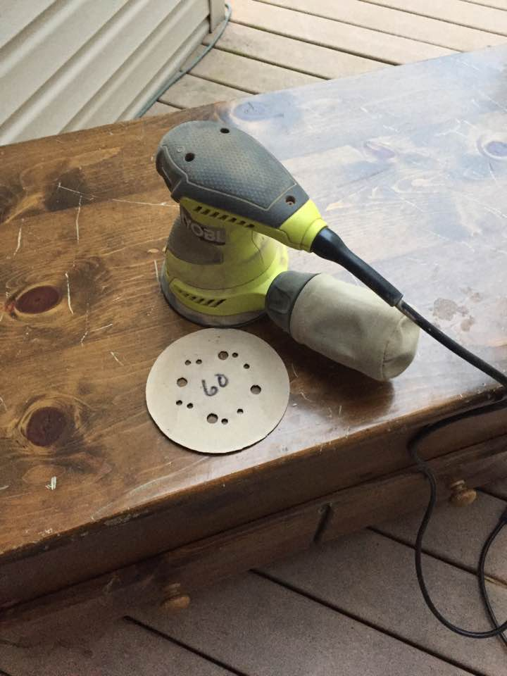 Preparing to smooth the wood with an orbital sander.