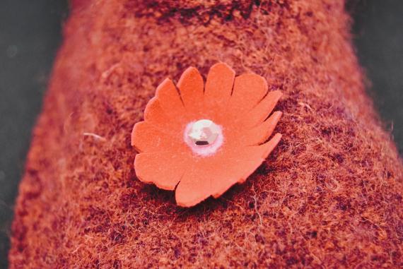 Kuvassa on punainen tossu, jossa on punainen kukka nahasta.