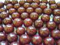 Several spherical dark red aniseed balls on a bright silver tray on a dark background.