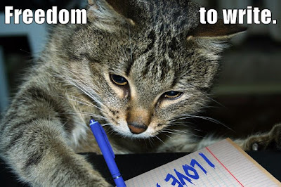 cat holding felt-tip pen. text: Freedom to write.