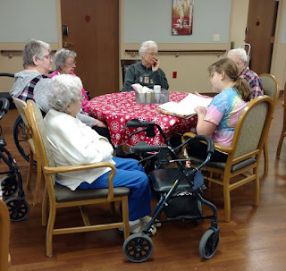 a young person reads to a table full of 5 seniors