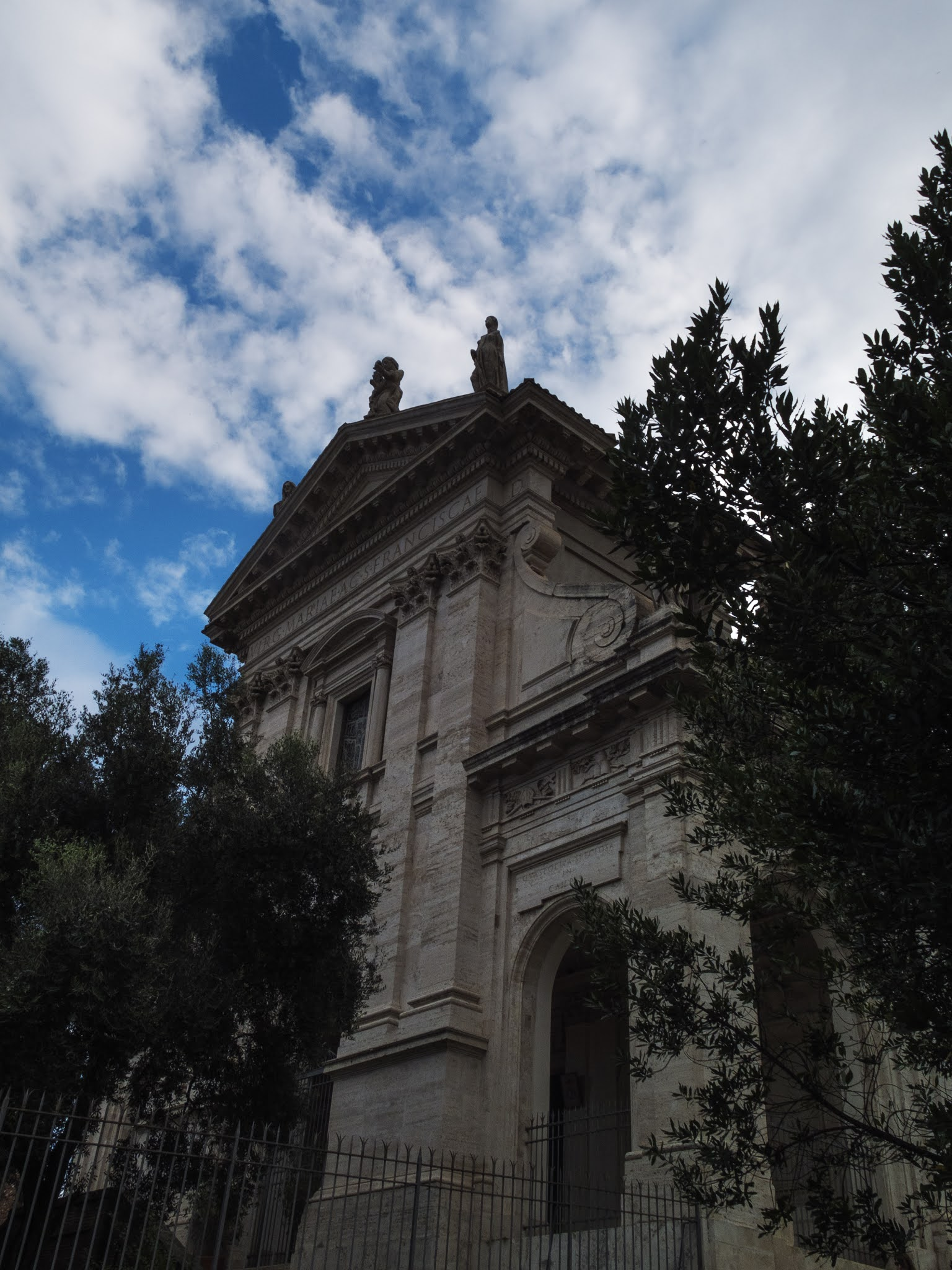 Basilica di Santa Francesca Romana surrounded by trees with a blue, cloudy sky above.