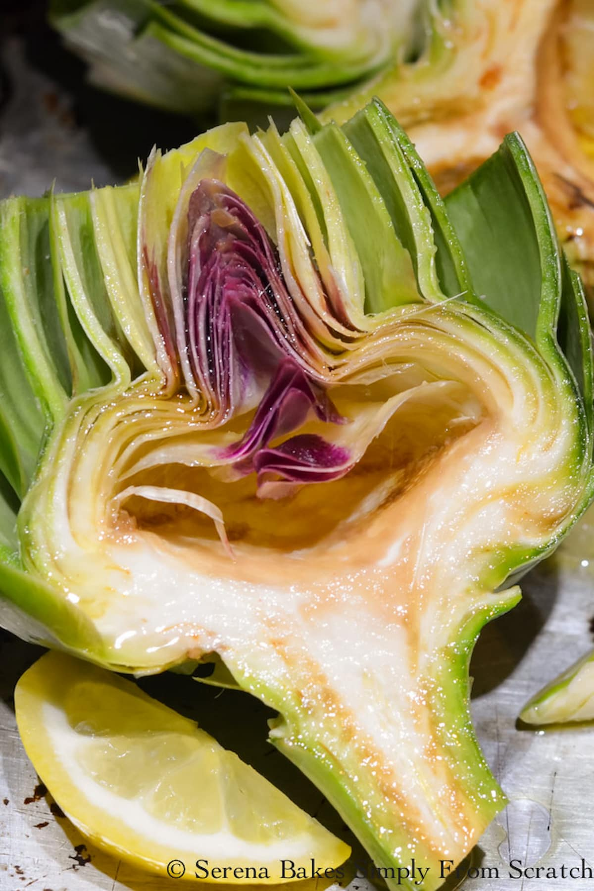 An Artichoke cut in half and trimmed up. The choke is removed from the center of the artichoke on a cookie sheet with lemon slices.