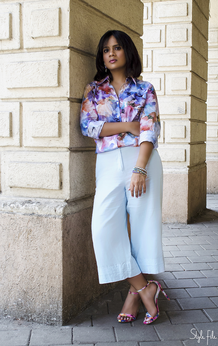 A female fashion blogger from India wears a pastel printed shirt with blue culottes and floral print high heels with dangling earrings, glossy lips and purple eye makeup for her fashion blog Style File