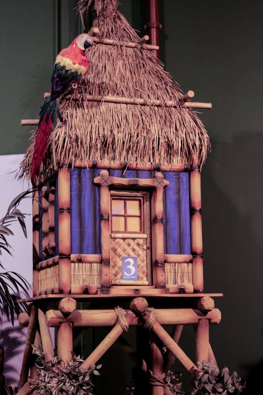 a fake tiki hut that has a fake parrot perched on top of it at hole 3 in the golf course