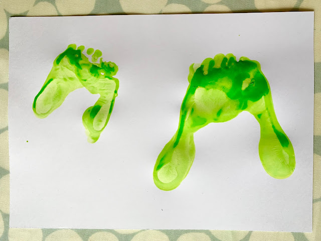 Two pairs of green overlapping footprint feet for dinosaur heads