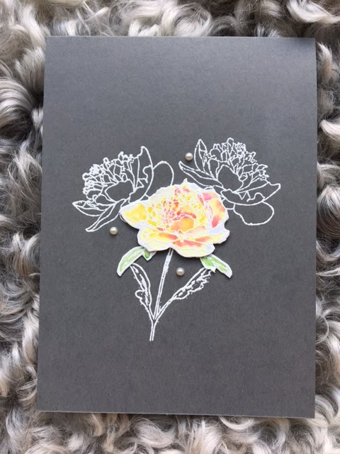 Heat embossing in white on dark cardstock with watercolored flower