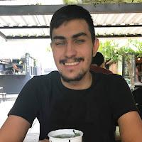 Gustavo Torniero está sentado e segurando um copo.