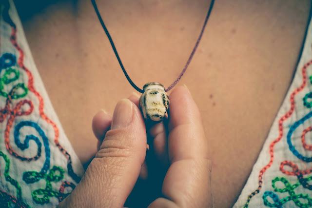 Mulher usando colar difusor em formato de ânforacom bata colorida
