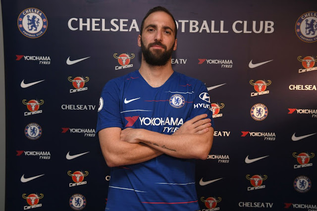 Higuain pose for a picture in a chelsea jersey after completing his move to stamford bridge on loan.