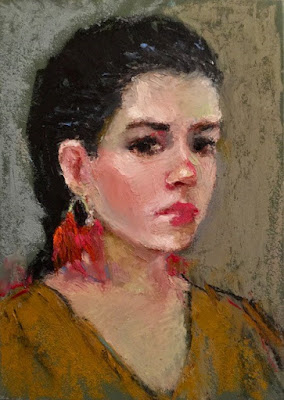 black haired woman with red feather earrings