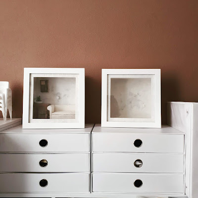 Two sets of white cardboard storage drawers against a mushroom-brown wall. On top are two white box frames, one containing a 1/12 scale sofa, side table, art work and pot of catci, the other is empty. Next to the drawers is a white ring binder.