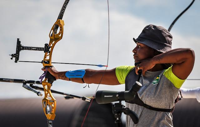 Ane Marcelle atira uma flecha com um arco amarelo e preto. Ela é uma mulher negra, com tranças no cabelo. Ane veste uma camiseta cinza com mangas amarelas e um chapéu