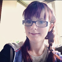A caucasian young woman with red hair with a fringe and styled in two braids. Se is wearing glasses and is smiling at the camera.