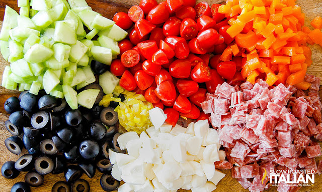 Tuscan Pasta Salad ingredients on a cutting board: cucumbers, olives, tomatoes, salami, cheese