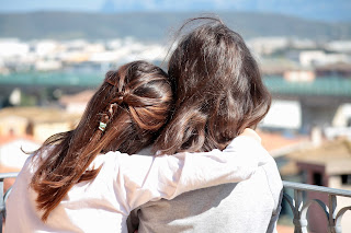 Two womens are hugging.