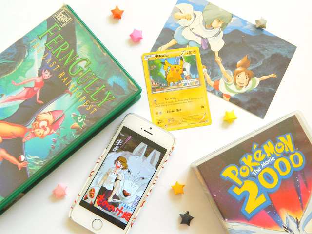 A photo showing two VHS tapes: Ferngully and Pokemon 2000, a Studio Ghibli image on a phone and postcard, a pikachu pokemon card and colourful paper stars