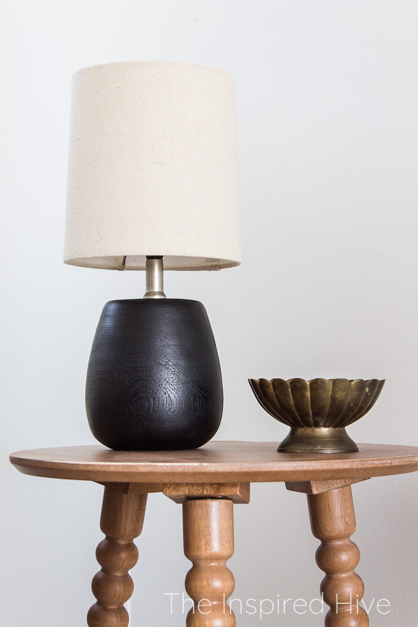 Spindle side table with mini black lamp and brass bowl