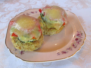 (2) breaded, baked eggplant slices topped with poached egg, roasted red peppers and spinach in a cream sauce topped with cheese on a pink china plate