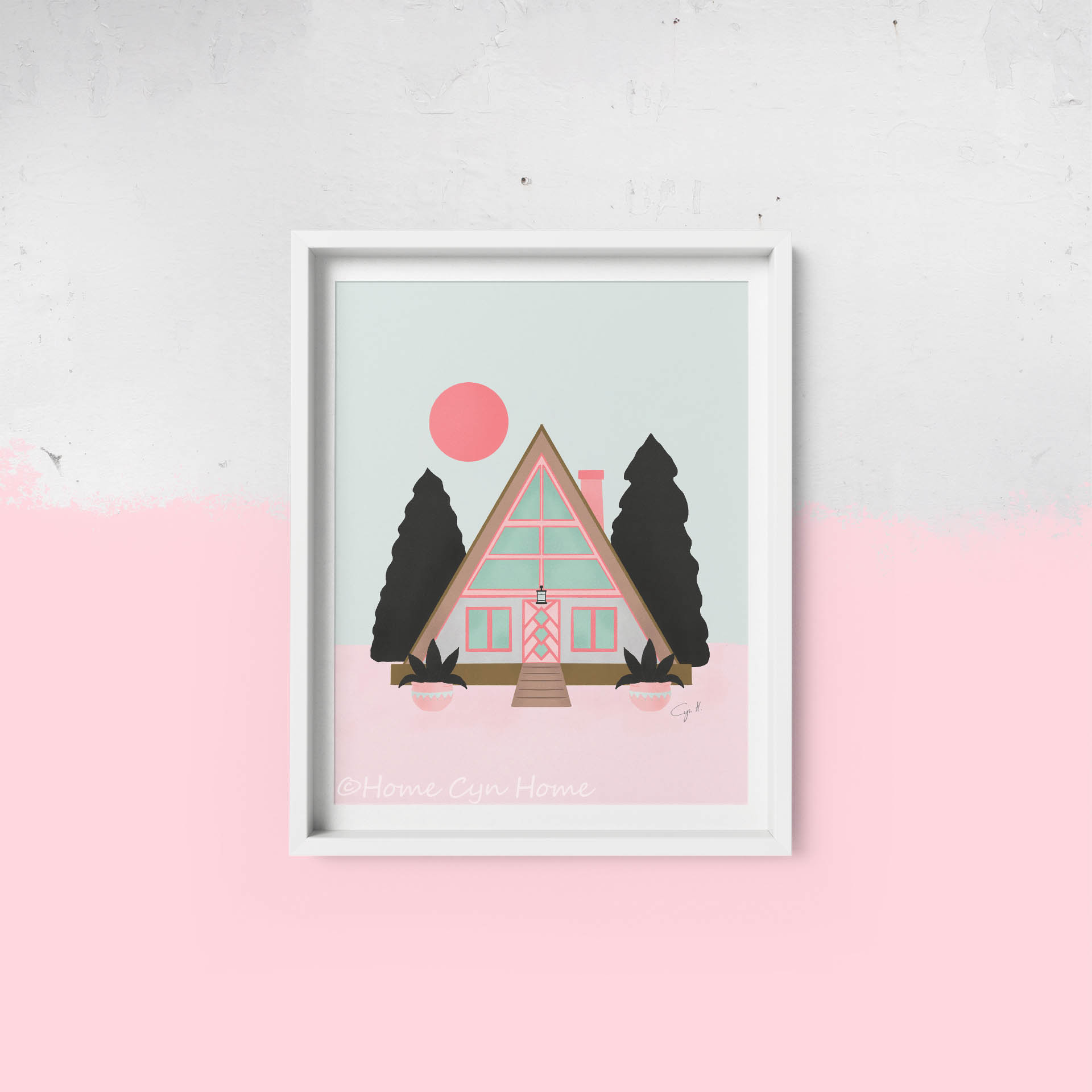 A cute pastel pink and mint A frame cabin surrounded by pine trees