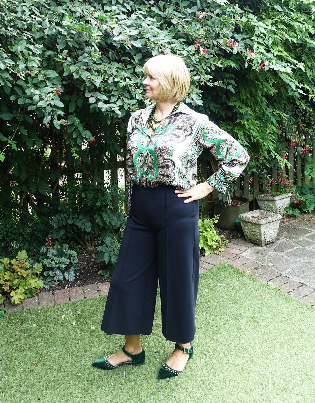 Black cropped trousers worn with a green print blouse, green flats and green beads