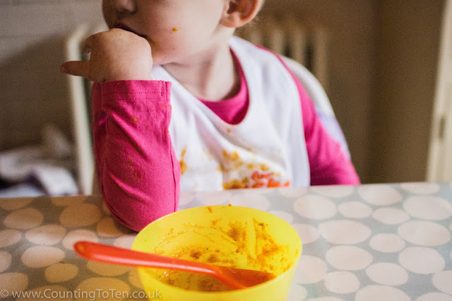 Toddler sitting at the table, resting her head on her hand with an empty bowl in front of her with the remains of some orange puree