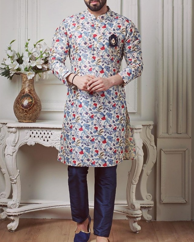 A man in floral print kurta-pyjama and jooti.