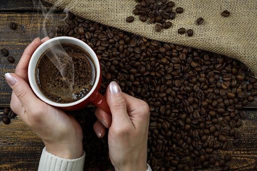Manos de mujer sosteniendo una taza de café con granos de café sobre la mesa