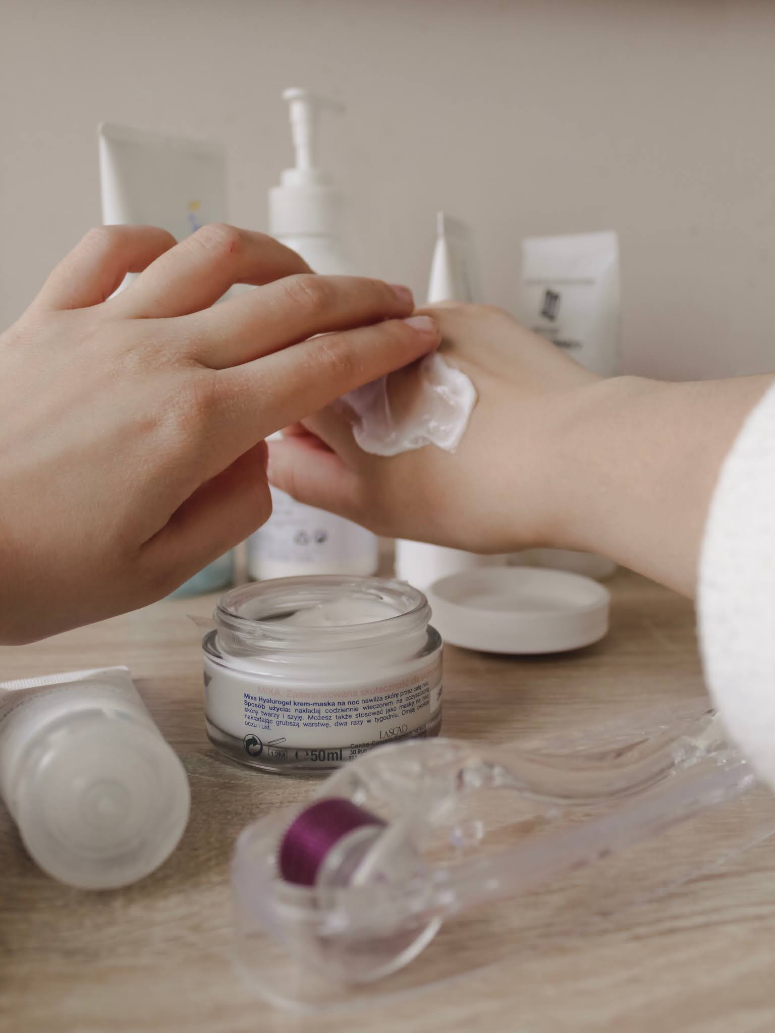 woman applying skincare cream to hand amongst other skincare items