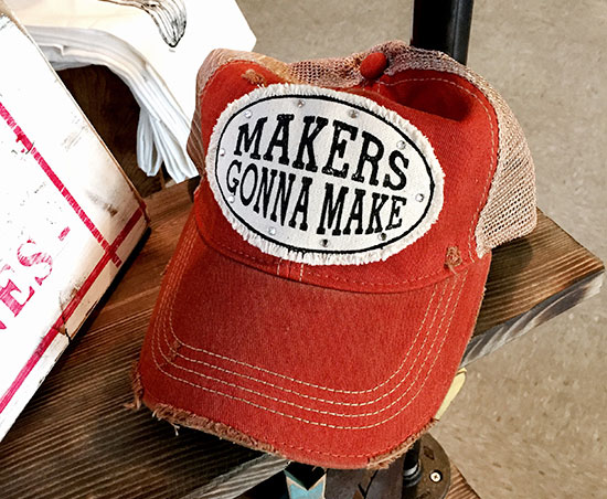 "Frayed red baseball cap with the words ""Makers Gonna Make"" on the front surrounded by sparkles."