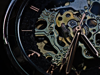 Close up of a watch shows intricate details of gears and springs.