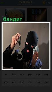 Бандит в маске и в руках держит наручники и деньги