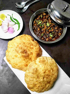 Serving chole bhature with onion, lemon slice and green chili for chole bhature recipe