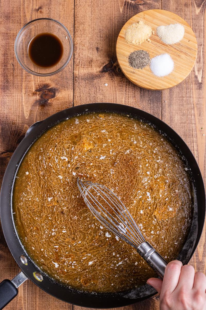 Whisking keto gravy in a skillet.
