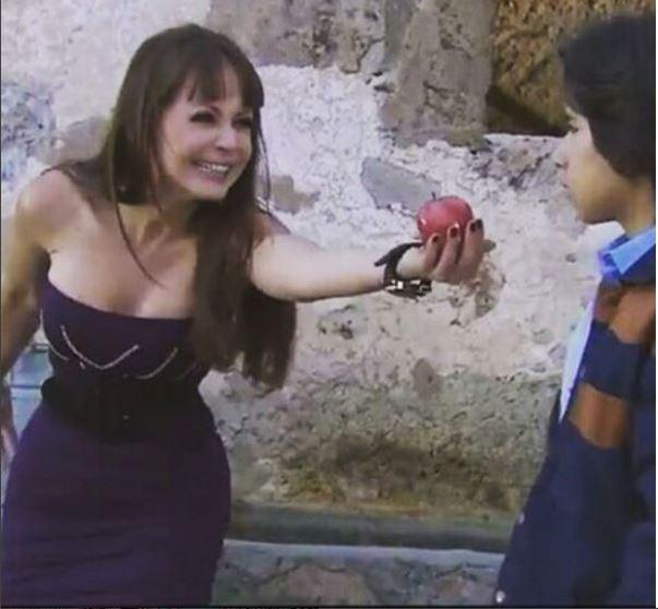 Ivana com vestido roxo oferecendo uma maça para o menino Jesus