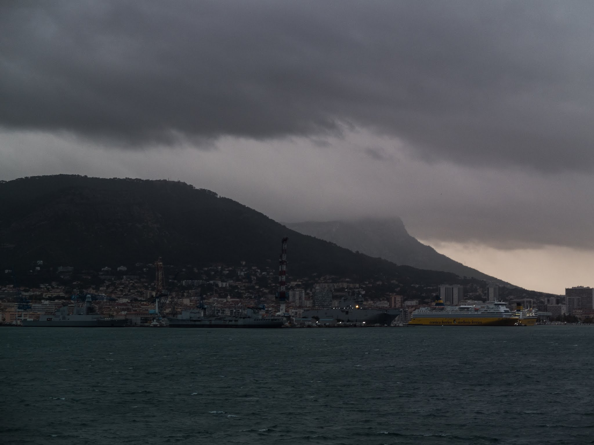 Sun rising behind the mountainside in Toulon harbour with dark clouds overhead.