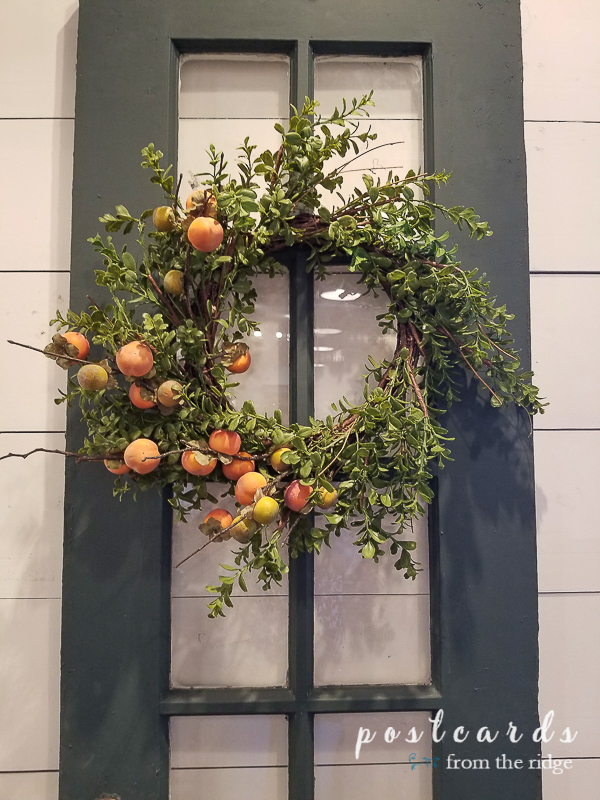 green painted windowpane door with wreath