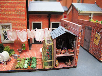 Miniature terrace house back yard with paper tape on the windows and washing on the line.
