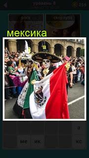 мужчина в сомбреро в Мексике идет по улице с флагом страны