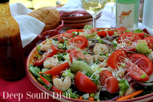 A combination Italian style salad made of romaine lettuce, shrimp, boiled egg, fresh tomatoes, olives, loads of veggies and dressed with a spicy tomato and garlic dressing.