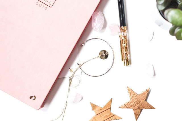 A silver bracelet, pair of gold stars, gold mascara, and baby pink notebook.