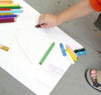 Närbild när barn målar med krita på papper på golvet.