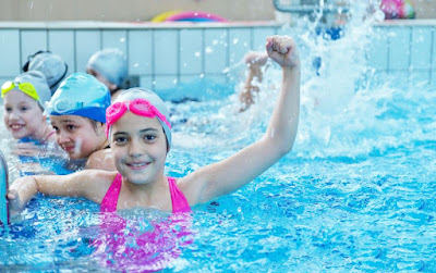 Image of a children in swimming lessons in the pool with on child giving a victory punch in the air. Managing children's behavior in the pool is important.