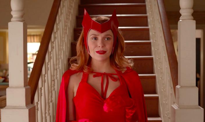 Imagem de capa: a personagem Wanda descendo de uma escada em sua casa, em uma fantasia que remete ao seu uniforme das HQs, um vestido vermelho sem alças, luvas vermelhas, uma capa vermelha e a tiara vermelha em formato de M em sua cabeça.