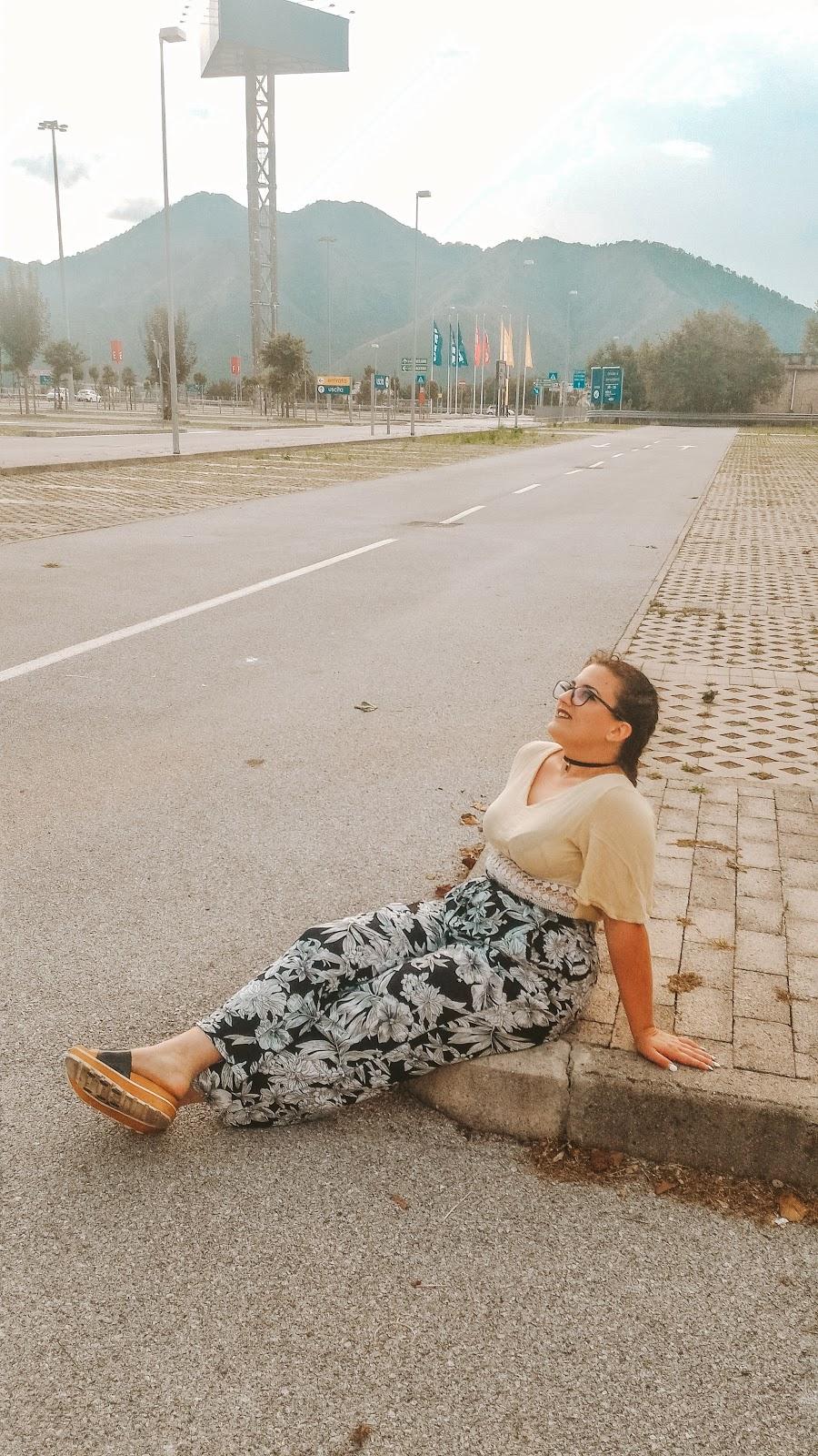 ragazza seduta in strada che guarda il cielo e sorride