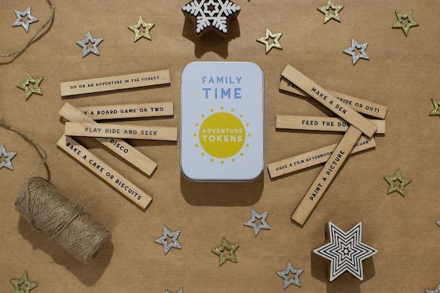 A tin with Family Time Adventure Tokens written on it next to 10 thin rectangles of wood with activity ideas on