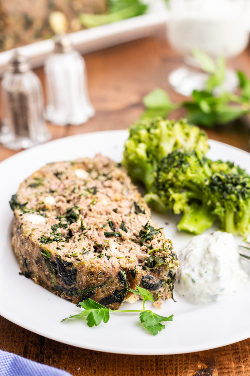 Photo of a slice of Keto Greek Style Meatloaf on a white plate with broccoli and Tzatziki sauce.