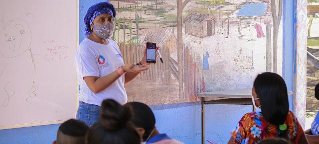 Una maestra explica cómo usar la aplicación para acceder al material educativo en los dispositivos móviles. La Guajira, ColombiaFundación El Origen