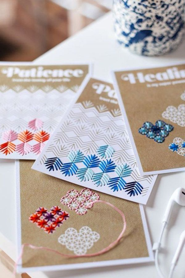 four embroidery kit cards with stitching in progress