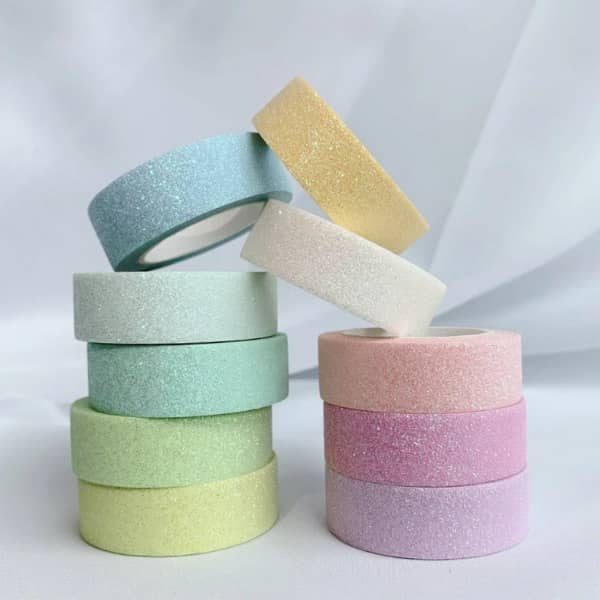 10 stacked glittered tape rolls in pastel colors